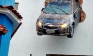 Motorista perdeu o controle do veículo e ficou com o carro pendurado no alto de prédio em Colatina