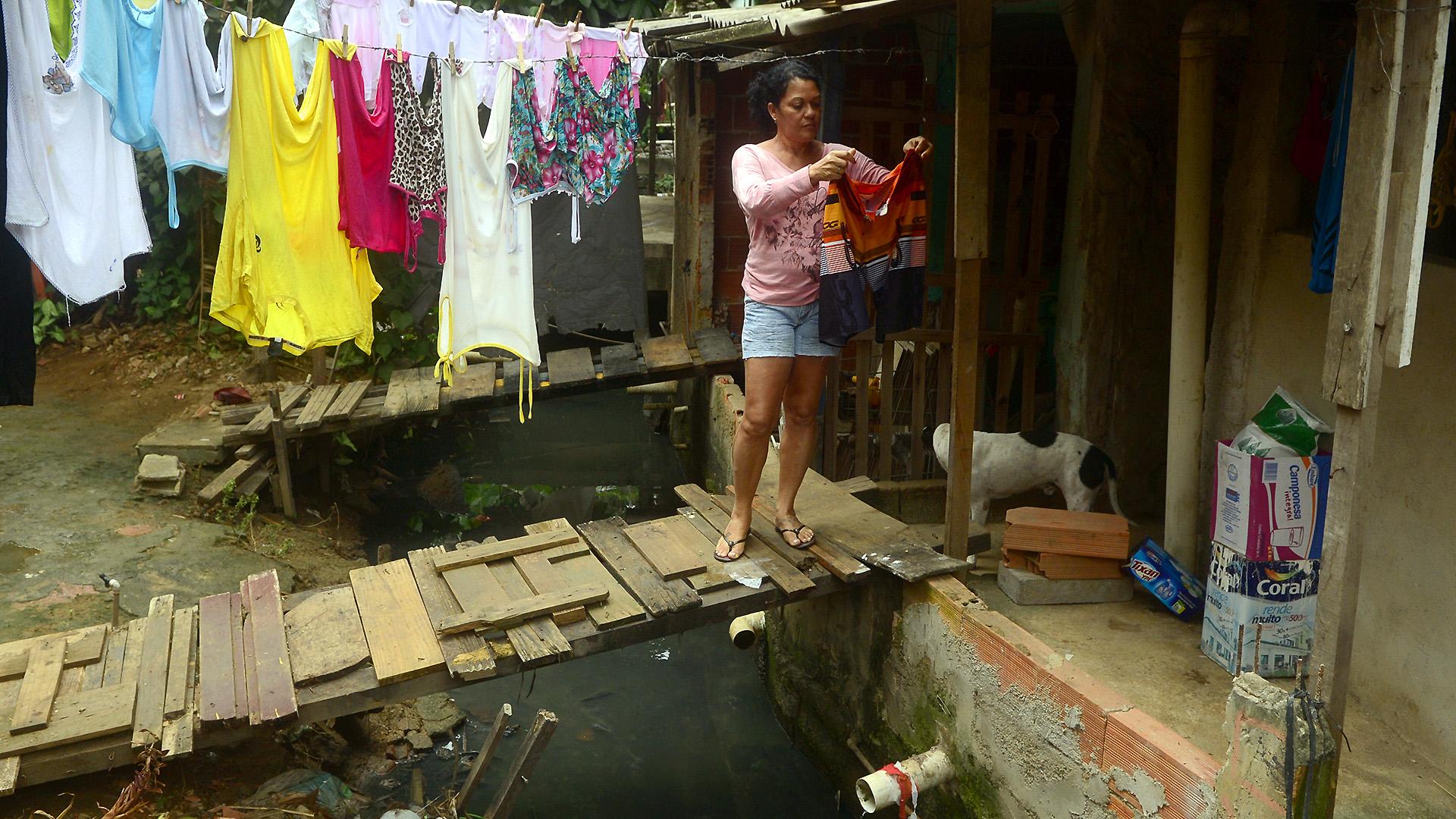 Em pé numa pinguela sobre valão, moradora estende roupas