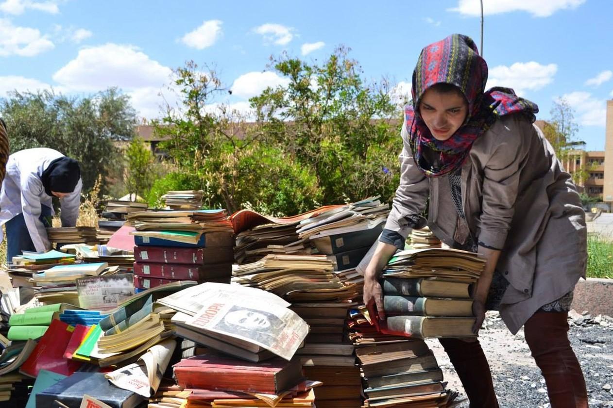Voluntária de Mossul ajuda a empilhar os livros retirados da Biblioteca Central da Universidade de Mossul, após o Estado Islâmico deixar o prédio, depois de 19 meses usando a universidade como ponto militar estratégico
