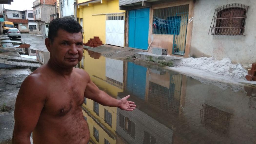 O motorista Charles da Silva mostra a rua alagada. Crédito: Caíque Verli