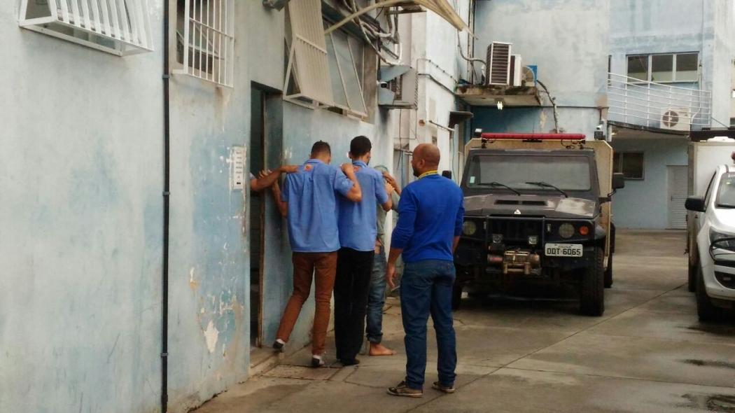 Funcionários de supermercado, de uniforme azul, são presos por furto. Crédito: Mayra Bandeira