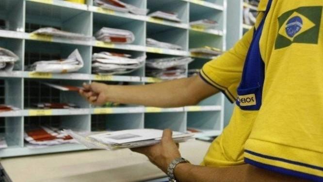 Funcionário dos Correios faz triagem da correspondência. Crédito: Agência O Globo