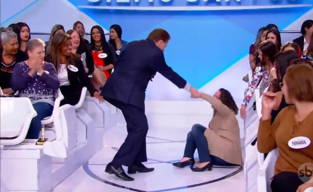 Mulher caiu ao sair da cadeira no programa ao vivo . Crédito: Reprodução/SBT