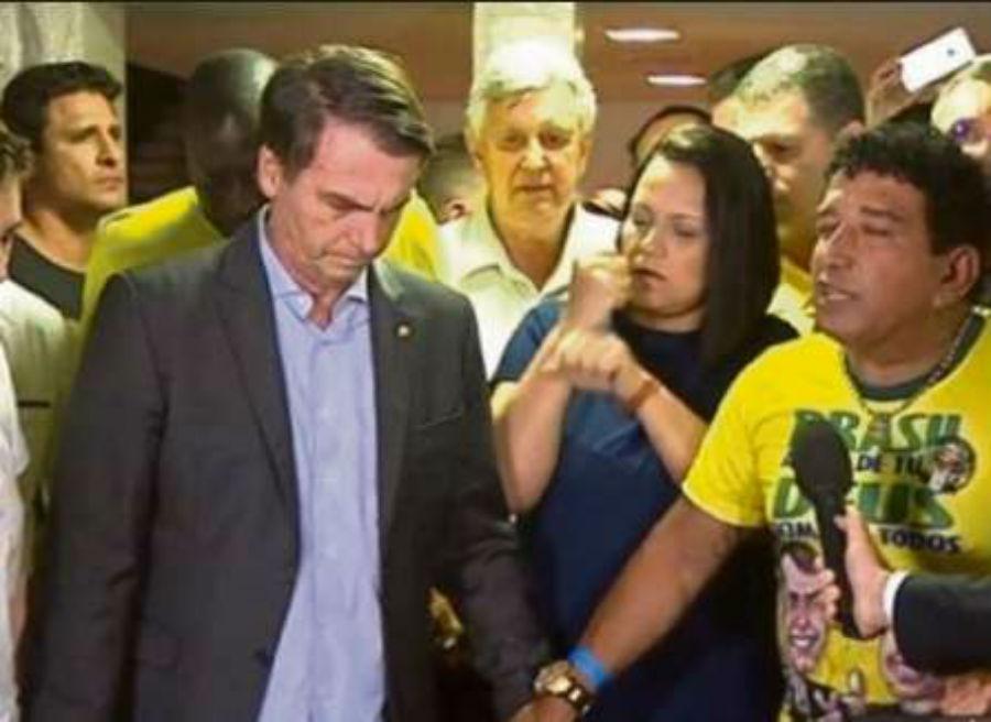 Magno Malta faz a oração da vitória segurando a mão de Jair Bolsonaro. Crédito: Reprodução de TV
