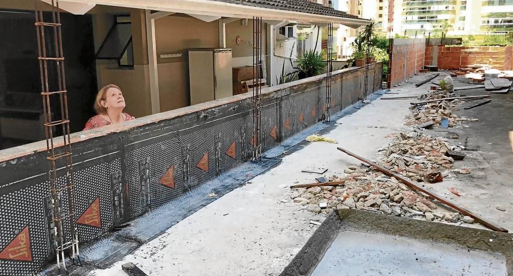 A varanda do apartamento de Neusa Ronconi, 62, fica ao lado da construção abandonada. A distância para ter acesso ao imóvel dela é de apenas um pulo   . Crédito: Kaíque dias