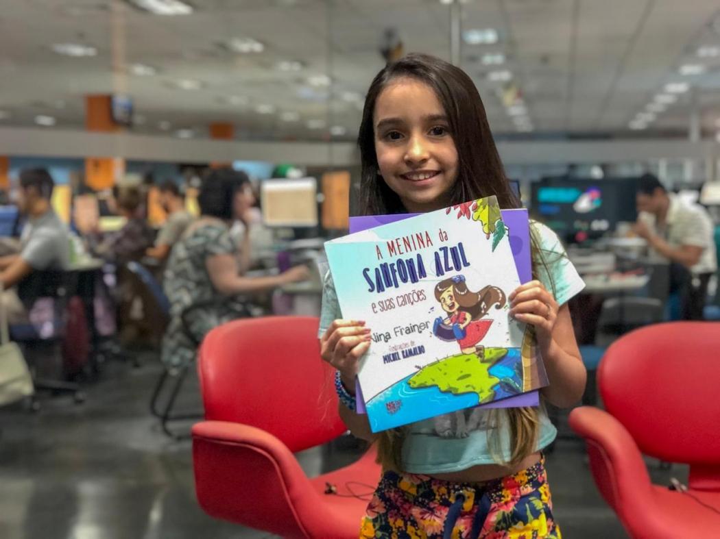"""A escritora Nina Frainer, de 10 anos, lembra de sua primeira obra, """"A Menina da Sanfona Azul"""". Crédito: Pedro Permuy"""