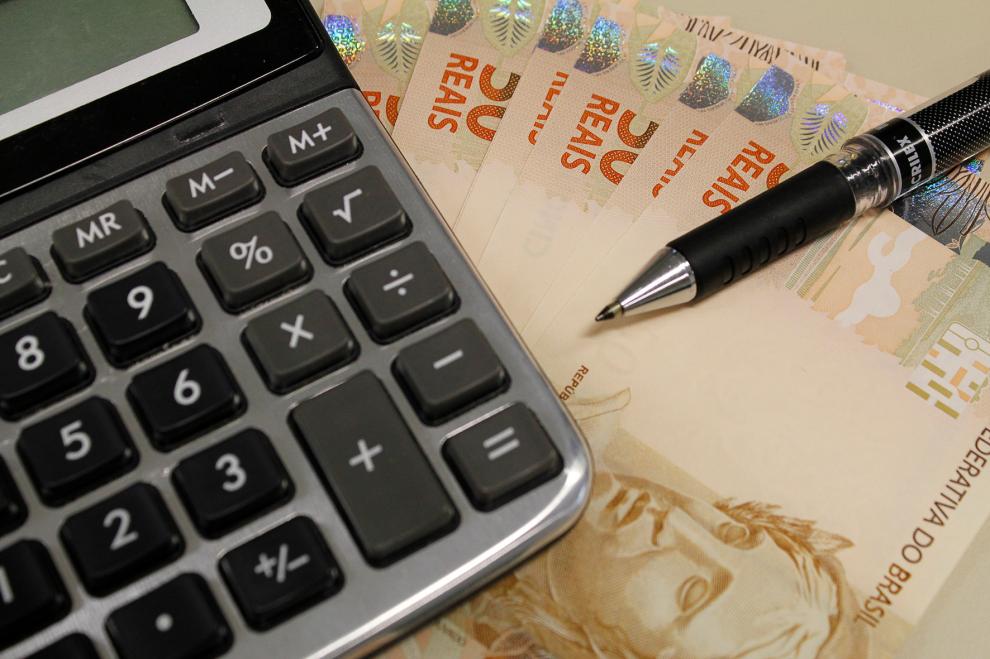 Calculadora e dinheiro: discussão da reforma tributária ganha corpo, mas há temos por parte dos Estados. Crédito: Divulgação